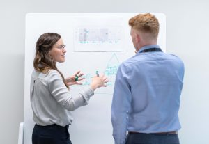 a packaging engineer talks to colleague in front of a whiteboard