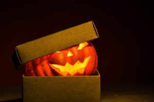 carved orange pumpkin with jack o lantern face lit up sitting inside brown cardboard box with lid with black background
