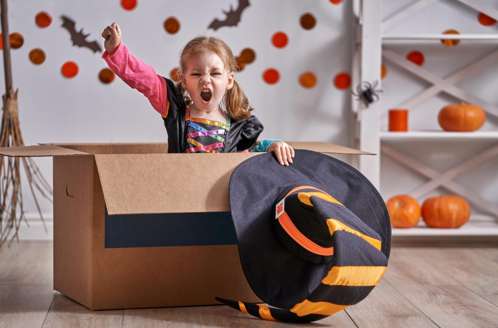 little girl sits in cardboard box cheering while wearing halloween witch costume with halloween decorations in background