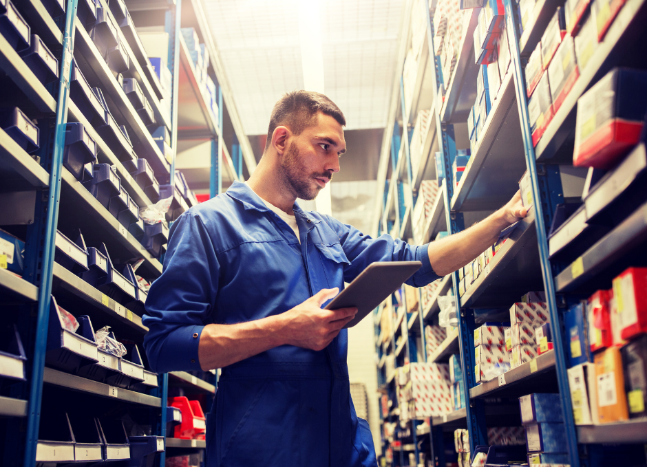 man in blue worker's jumpsuit searching for parts in plastic boxes on shelves