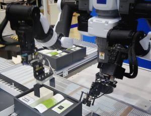 two collaborative robot arms place hair care products into black boxes on conveyor line